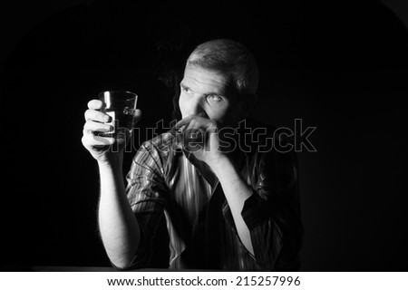 Man in a striped shirt at the age of forty-six years old holding a glass in his hand and smokes on the black background - stock photo