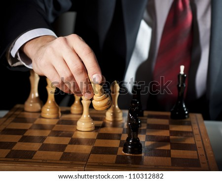 man in a suit and tie, playing chess, the success of the mind - stock photo