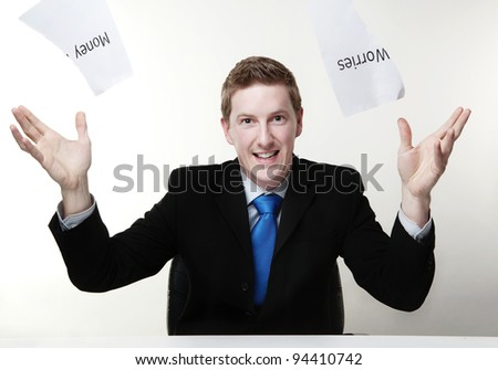 man in a suit sat at a desk just ripped up  a  piece of paper up with the words money worries printed on it and now throwing it away - stock photo