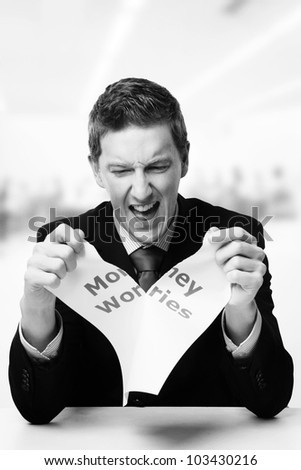 man in a suit sat at a desk ripping a  piece of paper up with the words money worries printed on it and looking happy doing so. - stock photo