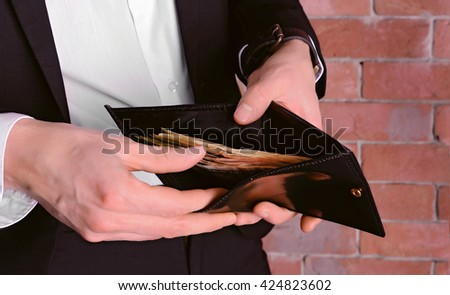 Man in a suit showing a purse with banknotes on brick wall background