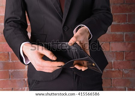 Man in a suit showing an empty purse on brick wall background - stock photo