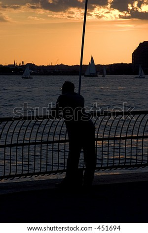 Man in a suit watching the sunset from Battery Park City (close-up)