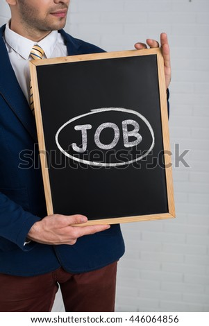 Man in a suit with a black board in his hands on a white background. Text JOB