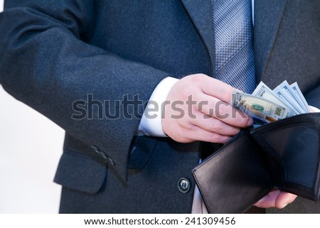 Man in a suit with a purse in his hands counting money - stock photo
