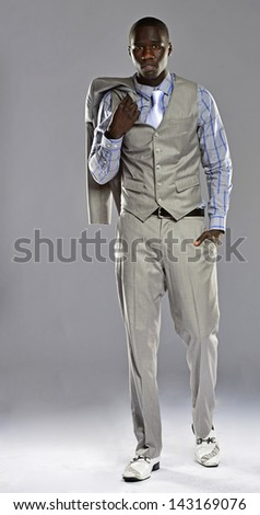 Man in a suit with his coat over his shoulder walking towards the camera. - stock photo