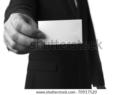 man in a suite and red tie holding a out a plain white business card for you to take - stock photo