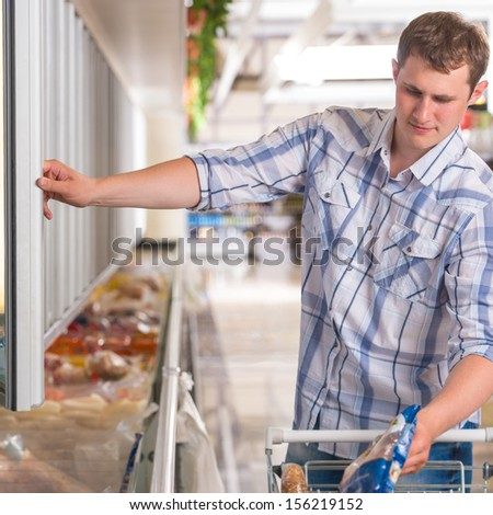 Man in a supermarket standing in front of the freezer looking for his favorite frozen food and preparing for thanksgiving dinner - stock photo