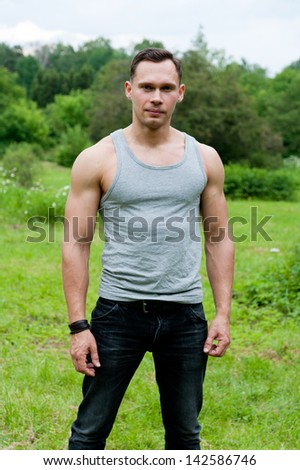 Man in a t-shirt stands on the grass in the park - stock photo