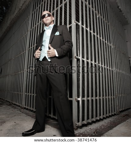 Man in a tuxedo posing by a metal enclosure - stock photo