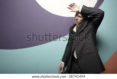 Man in a tuxedo wiping his sweat of his forehead - stock photo