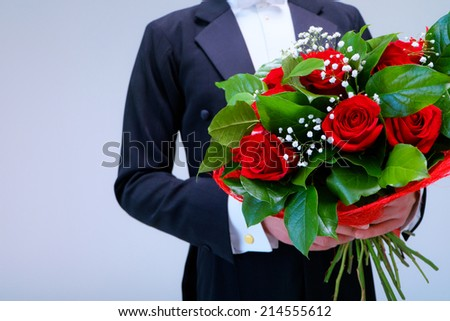 Man in a tuxedo with a bouquet - stock photo