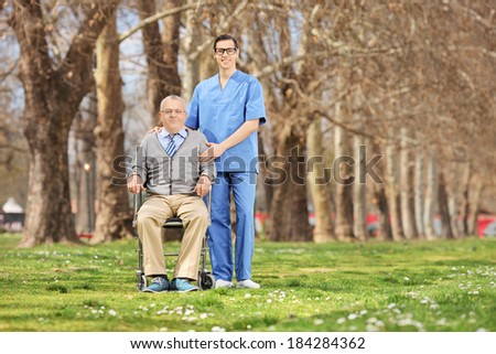 Man in a wheelchair and male nurse posing in park on a sunny day - stock photo