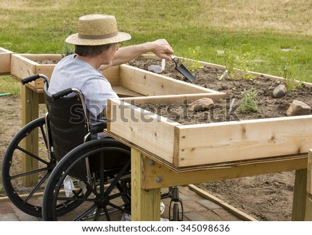 Man in a wheelchair working a garden at an enabling bench - stock photo