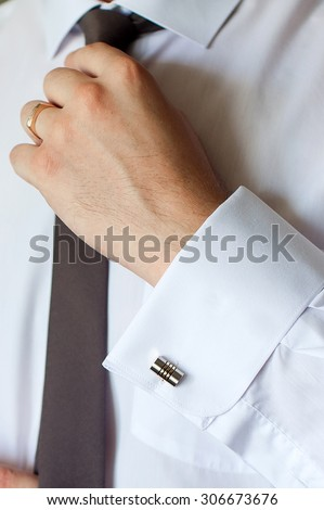 Man in a white shirt with cuff links, straightens his tie