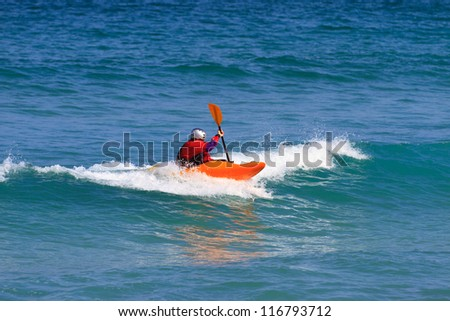 Man in a white water single kayak wearing a dry top and helmet as he rides the wave in open sea using his paddle to control his direction. - stock photo