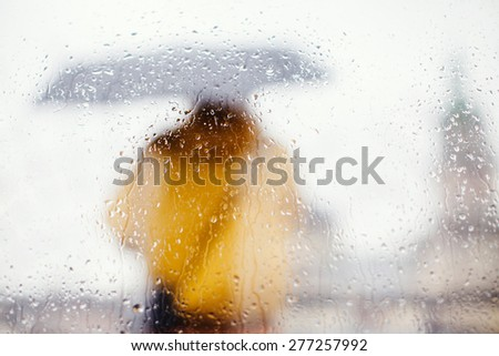 Man in a yellow jacket outdoors under umbrella silhouette through wet window - stock photo