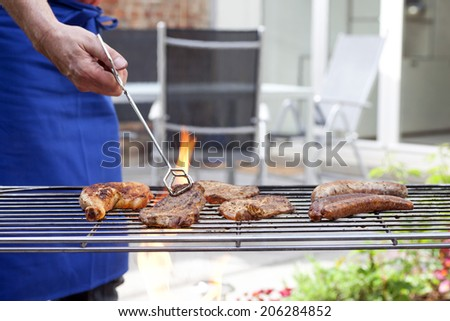 Man in apron at a barbecue grill preparing meat for a garden party - stock photo
