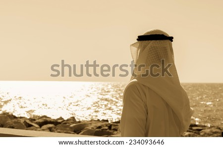 Man in Arab dress looks at the sea. Toned - stock photo