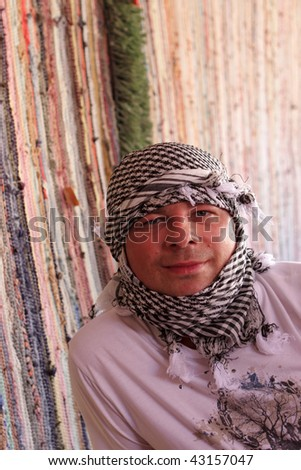 Man in arabic kerchief poses in Bedouin tent. Excursion in Egypt