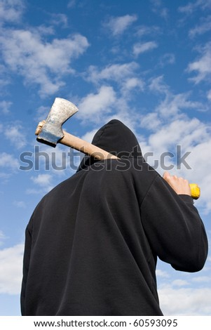 man in balaclava with an axe on sky background - stock photo