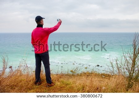 Man in baseball cap and pink windcheater takes photo by cellular phone. Windy day at ocean coast.