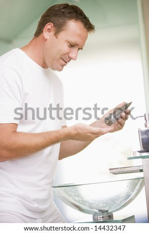 Man in bathroom applying aftershave - stock photo
