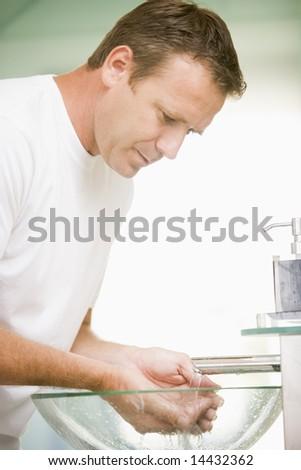 Man in bathroom washing hands - stock photo