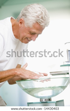 Man in bathroom with shaving cream smiling - stock photo