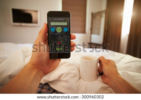 Man In Bed Looking At Health Monitoring App On Mobile Phone - stock photo