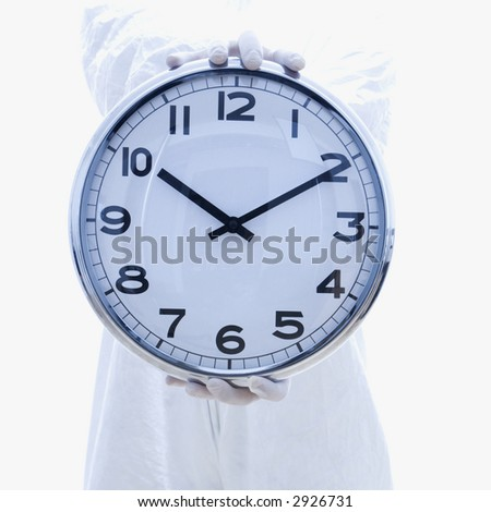 Man in biohazard suit holding out clock standing against white background.