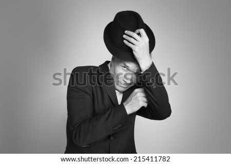 Man in black hat at the age of forty-six years old  looking at the camera on the background of a rough wall with texture - stock photo