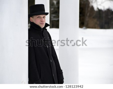 Man in black hat relies on white column