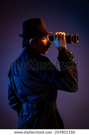 Man in black hat with binocular spying for somebody at dark background - stock photo