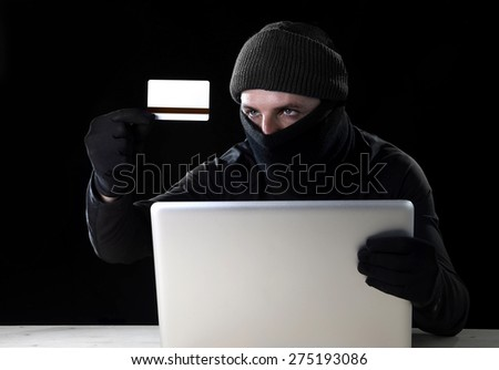 man in black holding credit card using computer laptop for criminal activity hacking password and private information cracking password too access bank account data in cyber crime concept