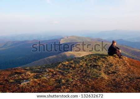 Man in black jacket sitting on top of a mountain and looks into the distance - stock photo