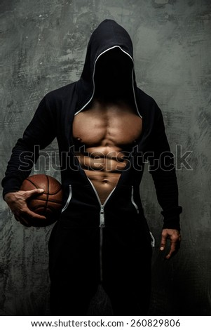 Man in black jacket with basket ball in a hands. Grey background. - stock photo