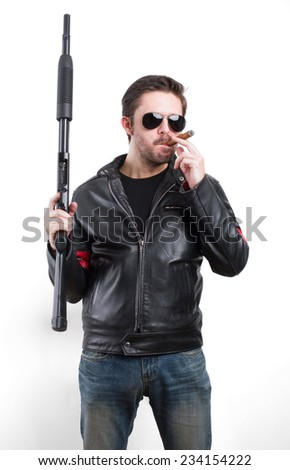 Man in black leather jacket and sunglasses with shotgun - stock photo