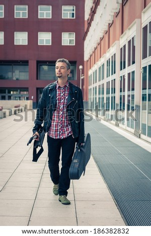 Man in black leather jacket walking in the street with electric guitar