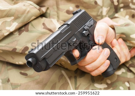 Man in black mask holding gun behind his back - focus on trigger - stock photo