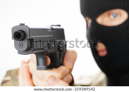 Man in black mask holding gun in front of him - stock photo