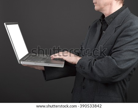 Man in black shirt and suit holding a laptop for working on keyboard