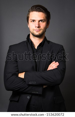 Man in Black Suit in front of a grey background looking serious - stock photo