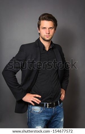 Man in Black Suit in front of a grey background looking serious