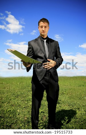 Man in black suit in the middle of the field - stock photo