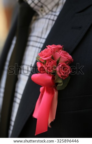 Man in black suit jacket with one small beautiful colorful soft aroma fresh wedding bouquet posy of many red rose flowers outdoor on checkered shirt background, vertical picture - stock photo