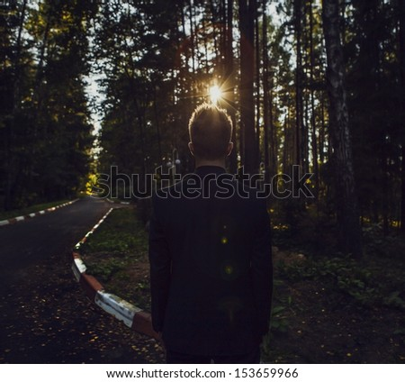 Man in black suit poses a back, looking at coming sun in park. - stock photo