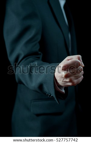 Man in black suit showing a fist
