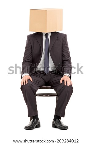 Man in black suit sitting on a wooden chair with a cardboard box on his head isolated on white background - stock photo