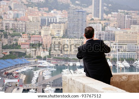 Man in black suit takes a picture of the city from the scenic overlook, Cote d'Azur, Monaco, Southern France. - stock photo